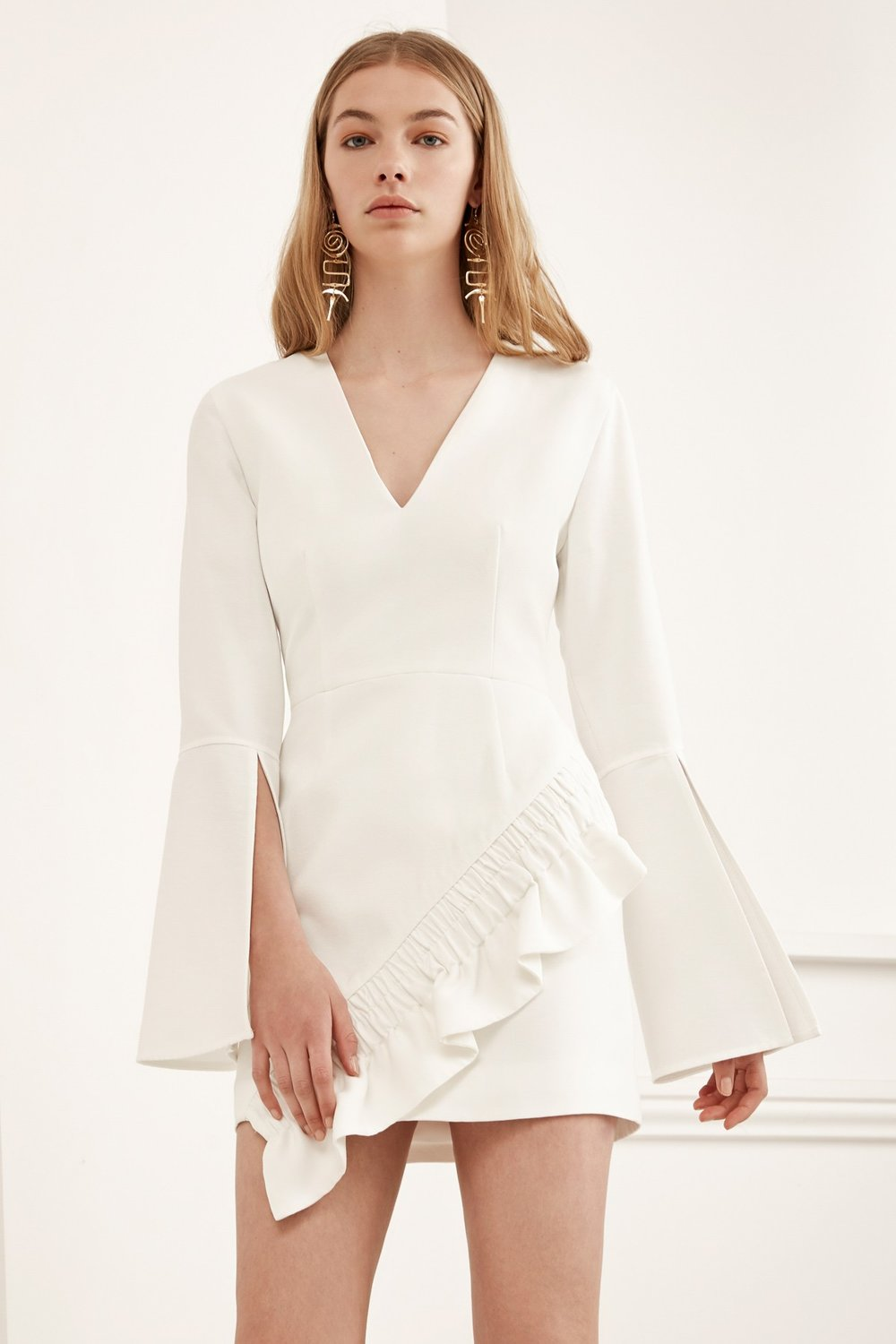 This ivory dress reminds us of what a futuristic Greek goddess would wear. The slit bell sleeves give this dress the look of a cape and the ruffle detail softens the structure of this piece. If you're searching for an unexpected dress to carry you through spring and summer, this is the perfect piece for you!