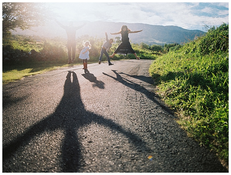 family-photographer-family-of-four-jumping-in-street-with-shadows.jpg