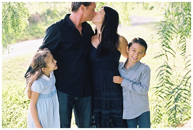 family-photographer-mom-dad-kissing-girl-boy-laughing.jpg