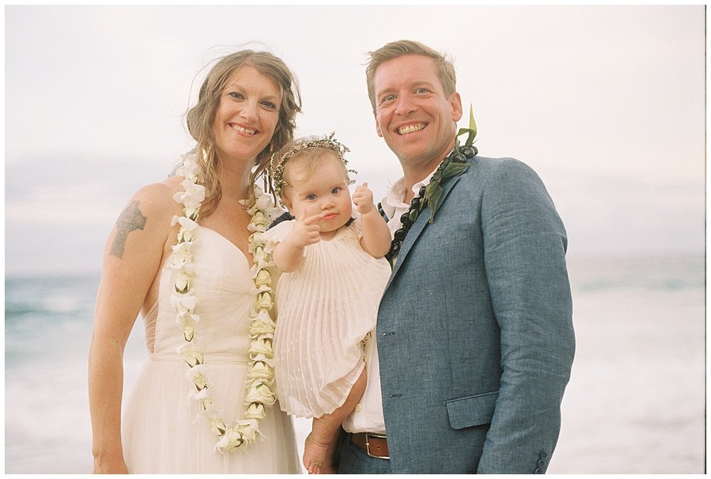 beach-elopement-bride-groom-baby-daughter-gives-thumbs-up-pointing-at-dad.jpg