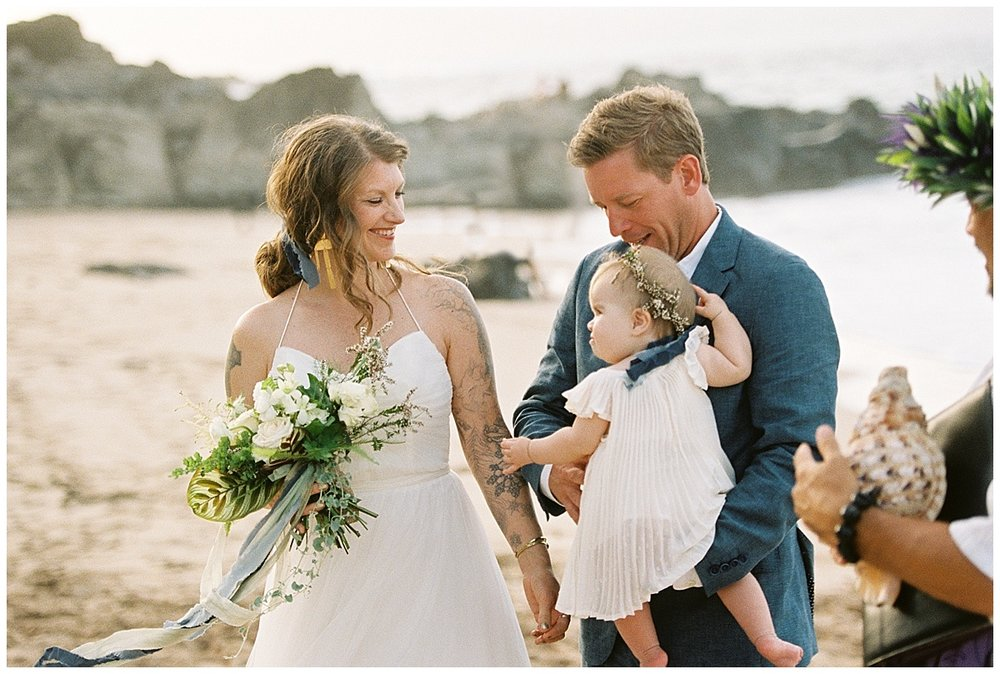 beach-elopement-bride-groom-daughter-baby-flowers-conch-shell-smiling.jpg