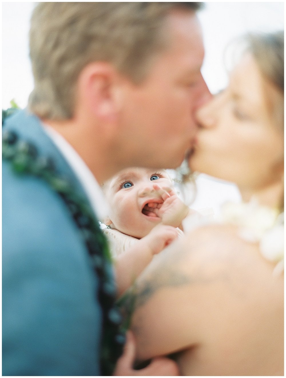 beach-elopement-bride-groom-kiss-while-daughter-watches.jpg