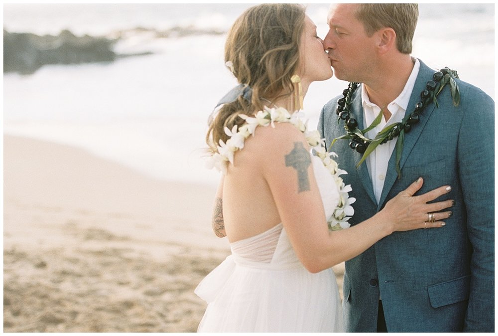 beach-elopement-bride-groom-tattoo-flower-lei-kiss.jpg