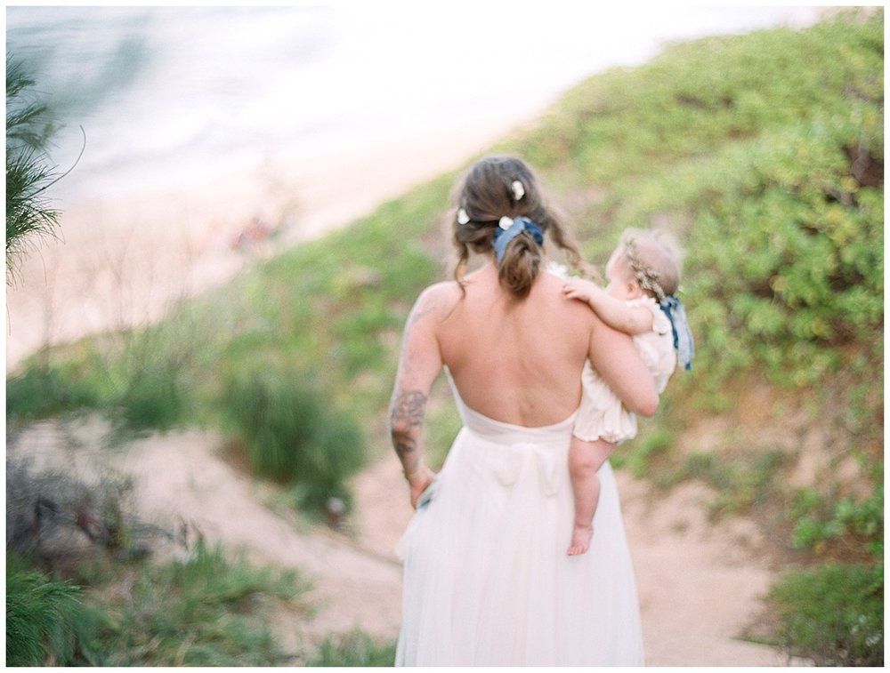 beach-elopement-bride-with-baby-girl-on-hip-walking-towards-beach.jpg