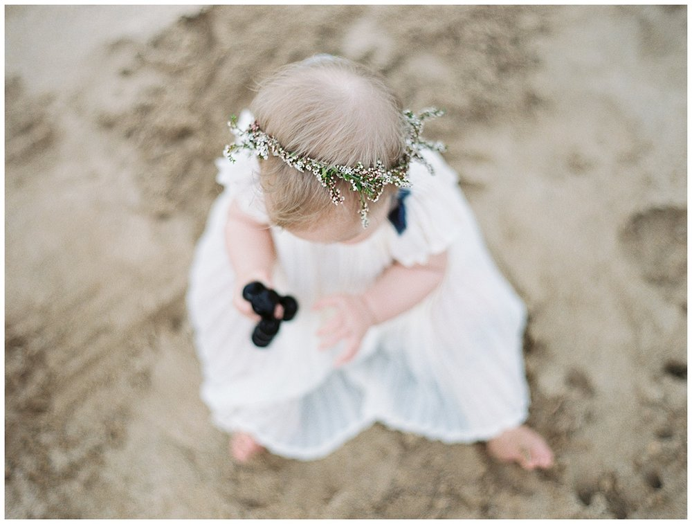 beach-elopement-flower-girl-holidng-kukui-nut-bracelet-flower-crown.jpg