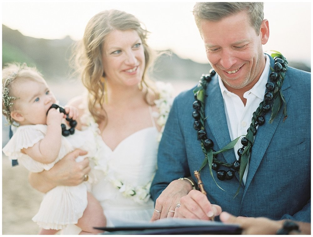 beach-elopement-groom-signing-license-bride-watching-and-smiling.jpg