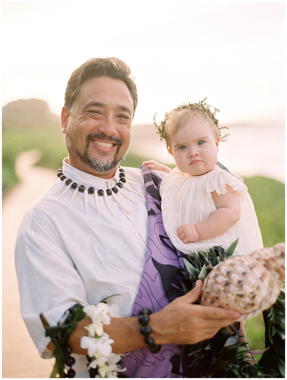 beach-elopement-hawaii-officiant-holding-baby.jpg