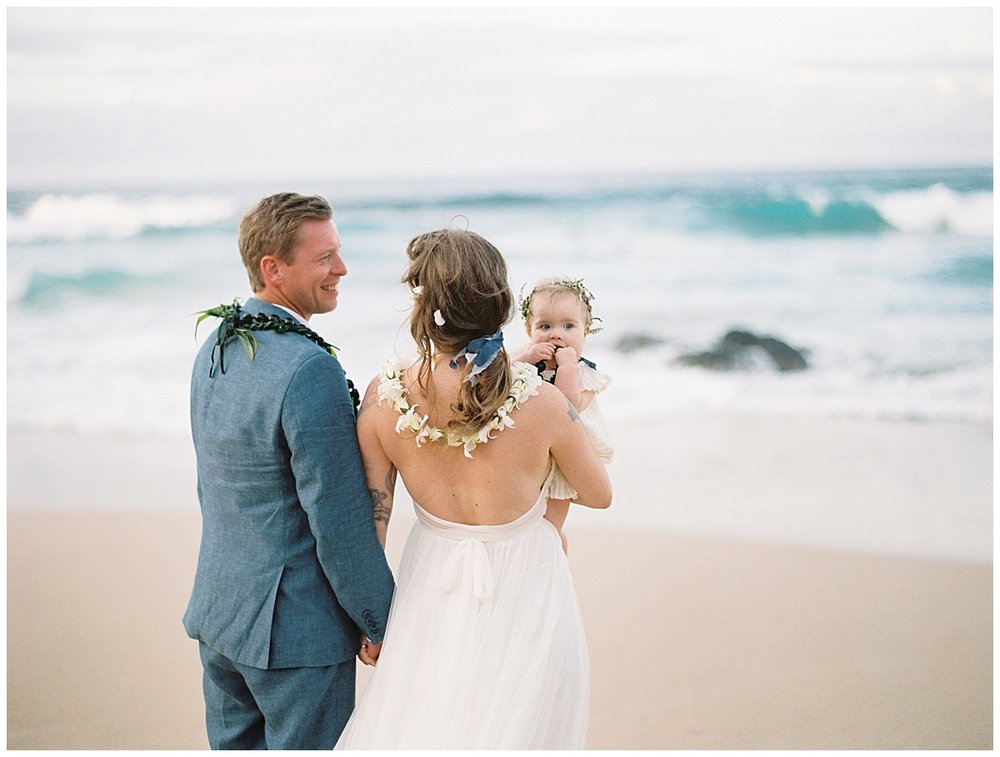 beach-elopement-maui-bride-groom-daughter-looking-at-each-other-by-ocean.jpg