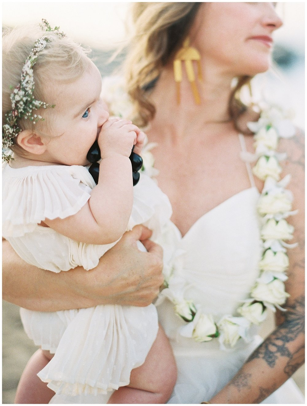 beach-elopement-maui-bride-holding-baby-daughter-white-flowers.jpg