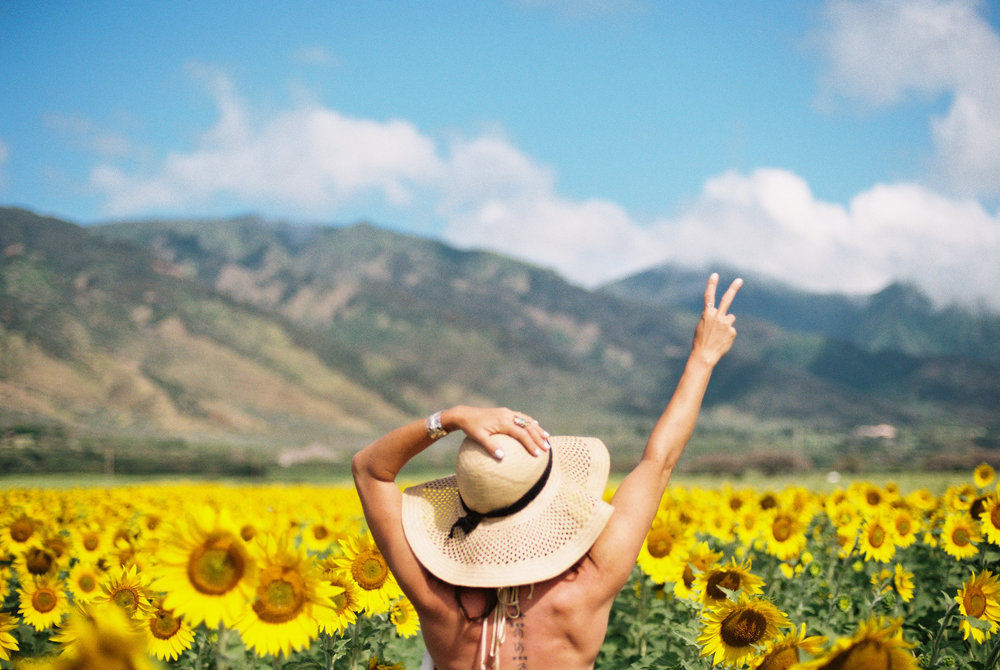 girl-sun-hat-peace-sign-sunflower-field-mountains-maui.jpg