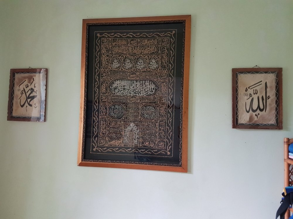 Islamic ornaments hang on the wall with names of of Allah SWT and Prophet Muhammed SAW in calligraphy.