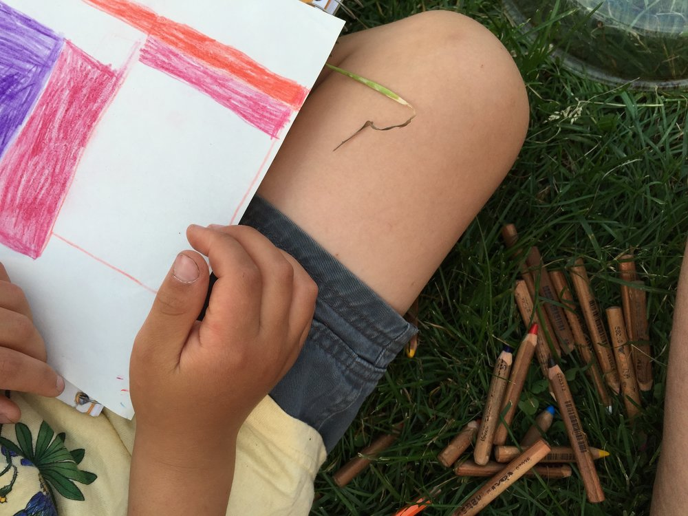 Jonah sits in the grass and draws.