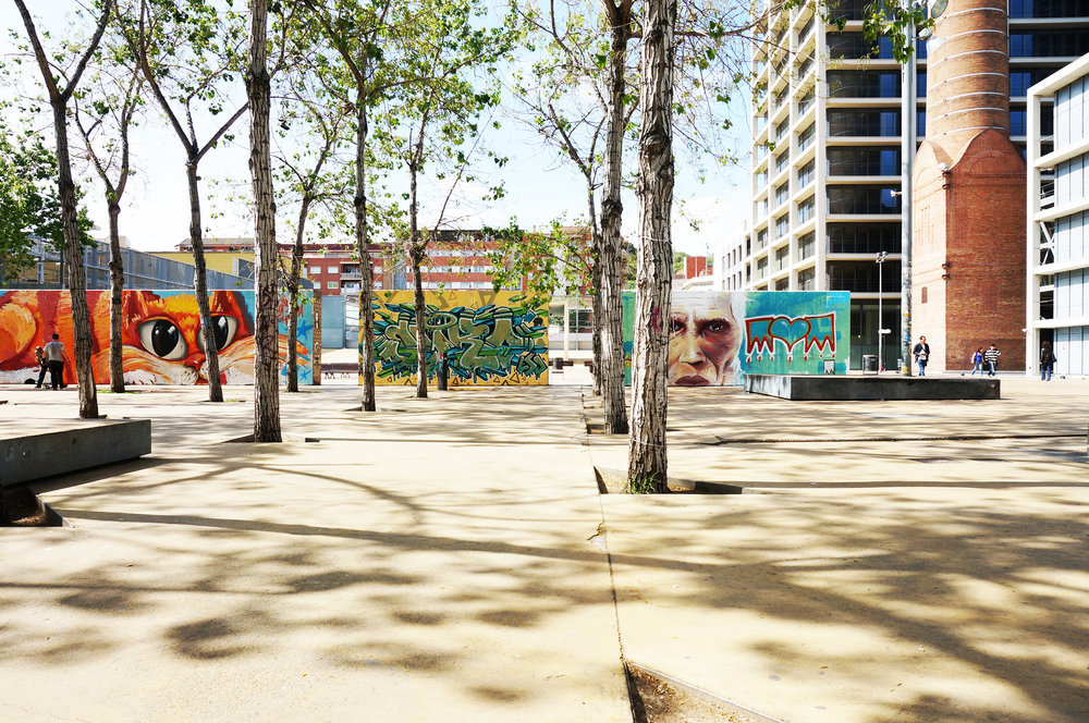 The image shows how a series of graffiti walls subdivide a large urban space in Jardins de les Tres Xemeneies in Barcelona and thus provides a flexible and multi-use space.
