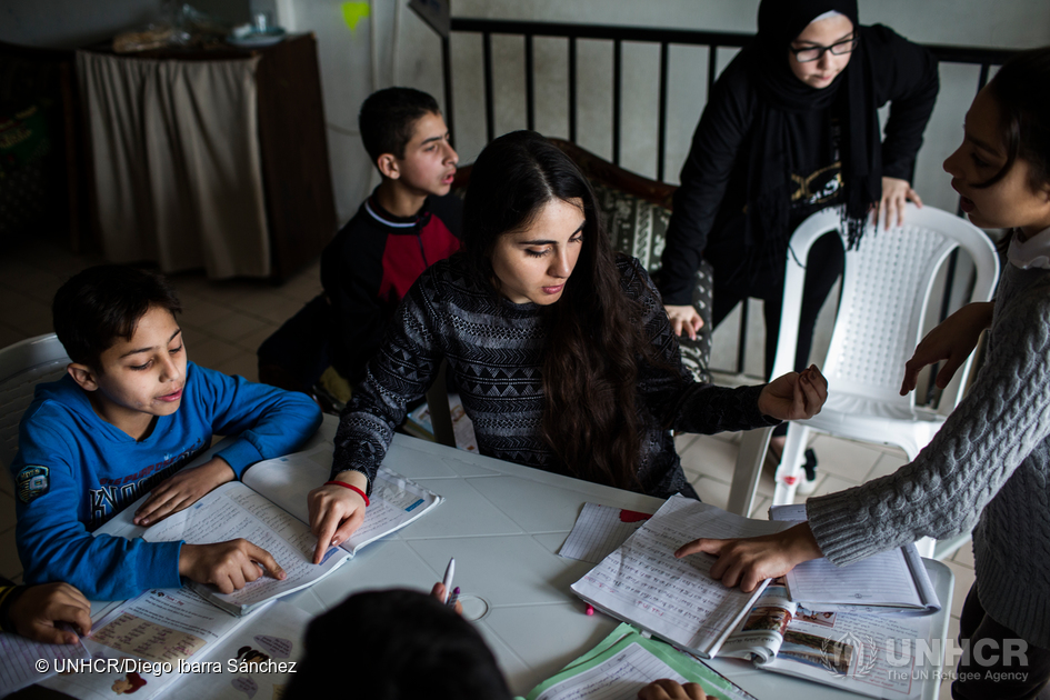 Nour teaches homework support lessons to a group of Young Syrians inside a makeshift school in Saida, Lebanon.