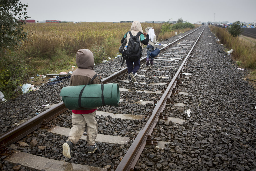 Three refugees walk along the train tracks running from Serbia into Hungary on their way to Austria