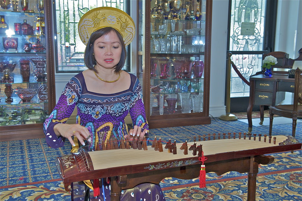 """Local Vietnamese-American artist, Julie Trinh Dang, entertains guests at the opening reception of """"Vietnamese Art"""" at the Czech Museum of Houston."""