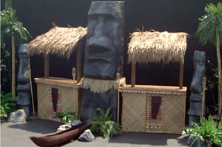 'TIKI BARS'   The Basic Tiki Bar measures approx 16' wide x 10' high x 5' deep and does  not  include the large statue in the center.   The Grand Tiki Bar measures approx 20' wide x 10' high x 5' deep and   does   includes large statue as seen in the photo.   Either setup is ideal for anyone that wants the coolest tiki bar at their luau event.   $650   — Basic Tiki Bar   $900   — Grand Tiki Bar