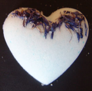 a gorgeous heart shaped bath fizzy with embedded cornflower petals