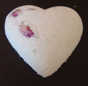 a heart shaped bath fizzy studded with a rose bud
