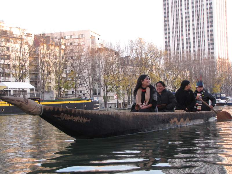 Grupo de Sarayaku navegando en el Sena (COP21), De: / Group of Sarayaku sailing at the Seine (COP21), from: https://amazonwatch.org/news/2015/1208-sarayakus-canoe-of-life-has-a-valiant-spirit