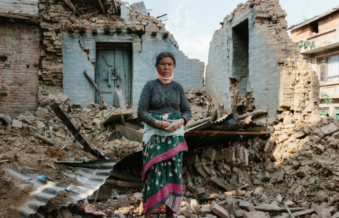 Nepalese women standing outside of her home
