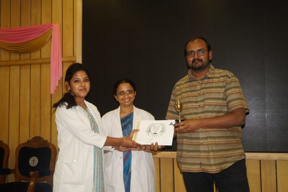 Dr.Nandhini getting the workaholic award from the Dean and the Director of Academics
