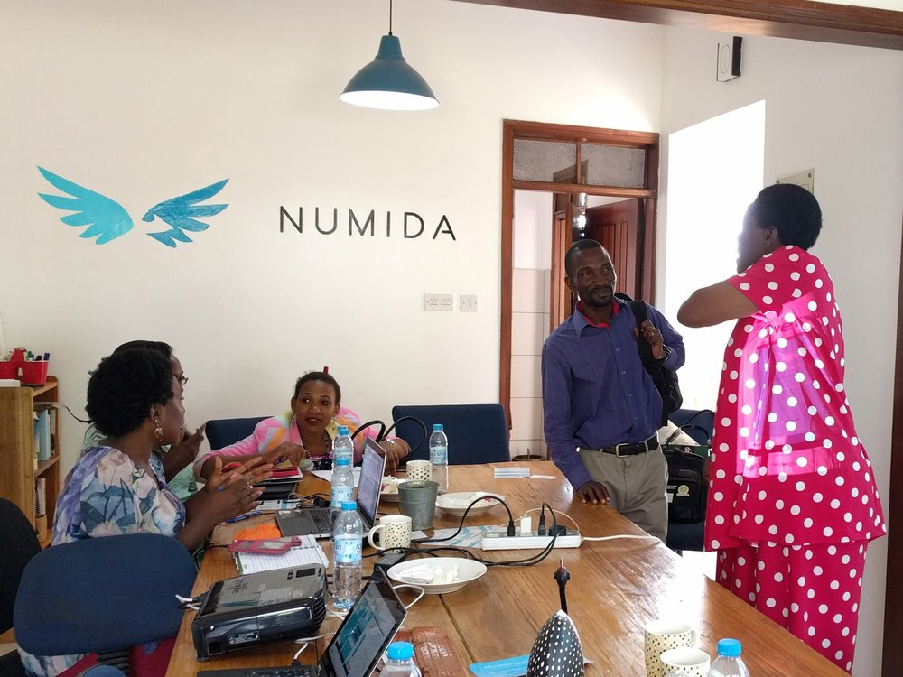 Entrepreneurs and staff members talk inside the Numida office in Kampala, Uganda.