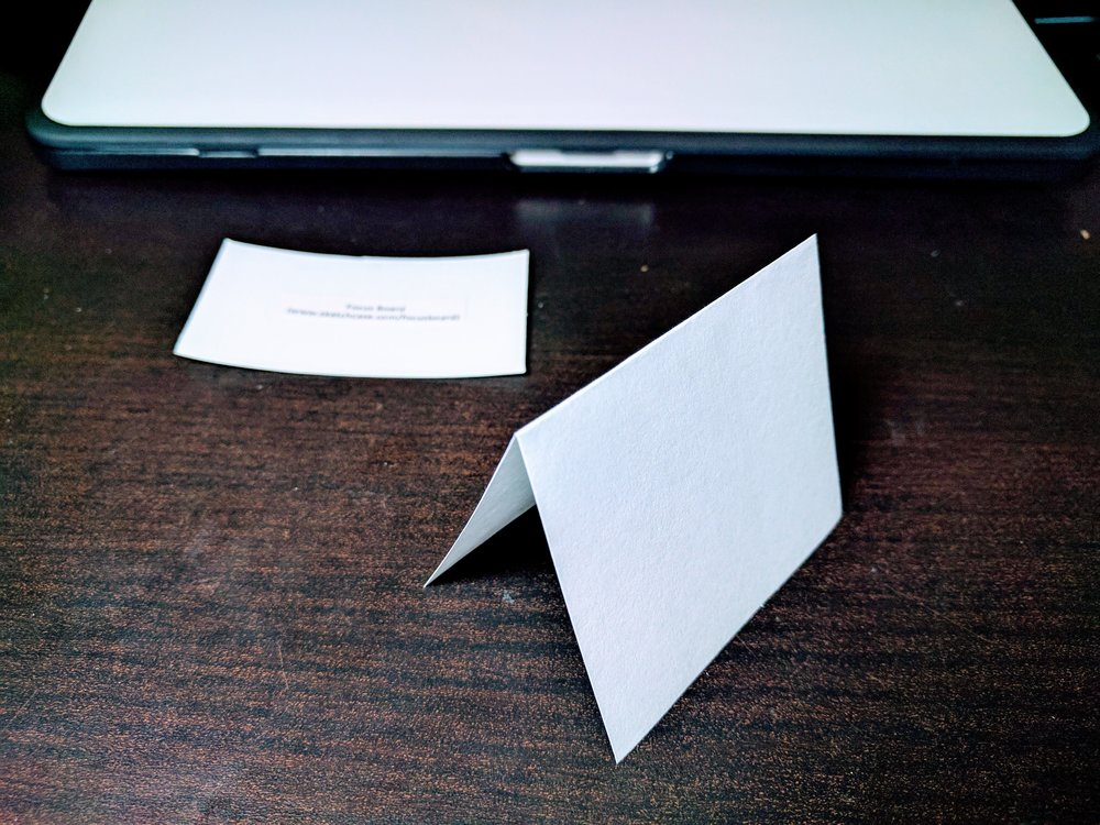 Fold the index card in half.