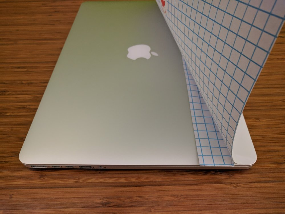 Start with the long edge. Peel off about an inch of the sticker and lightly fold the paper backing. Apply the sticker right at the edge of the laptop as seen in the picture.