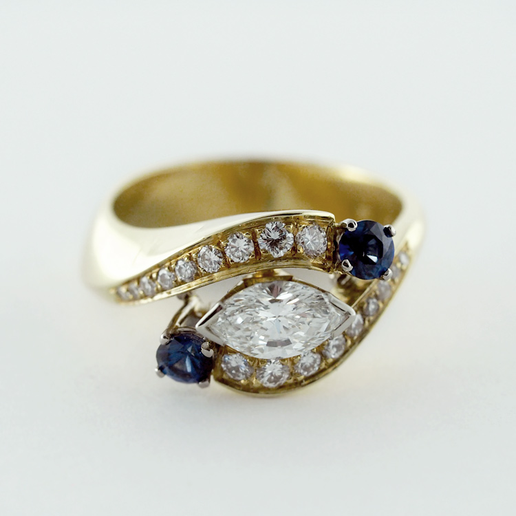 $9,834<br>18K Yellow Gold, <br>Centre Stone Marquise<br> Cut Diamond,<br> 2 Blue Sapphire,<br> 16 Brilliant Cut<br> Diamonds