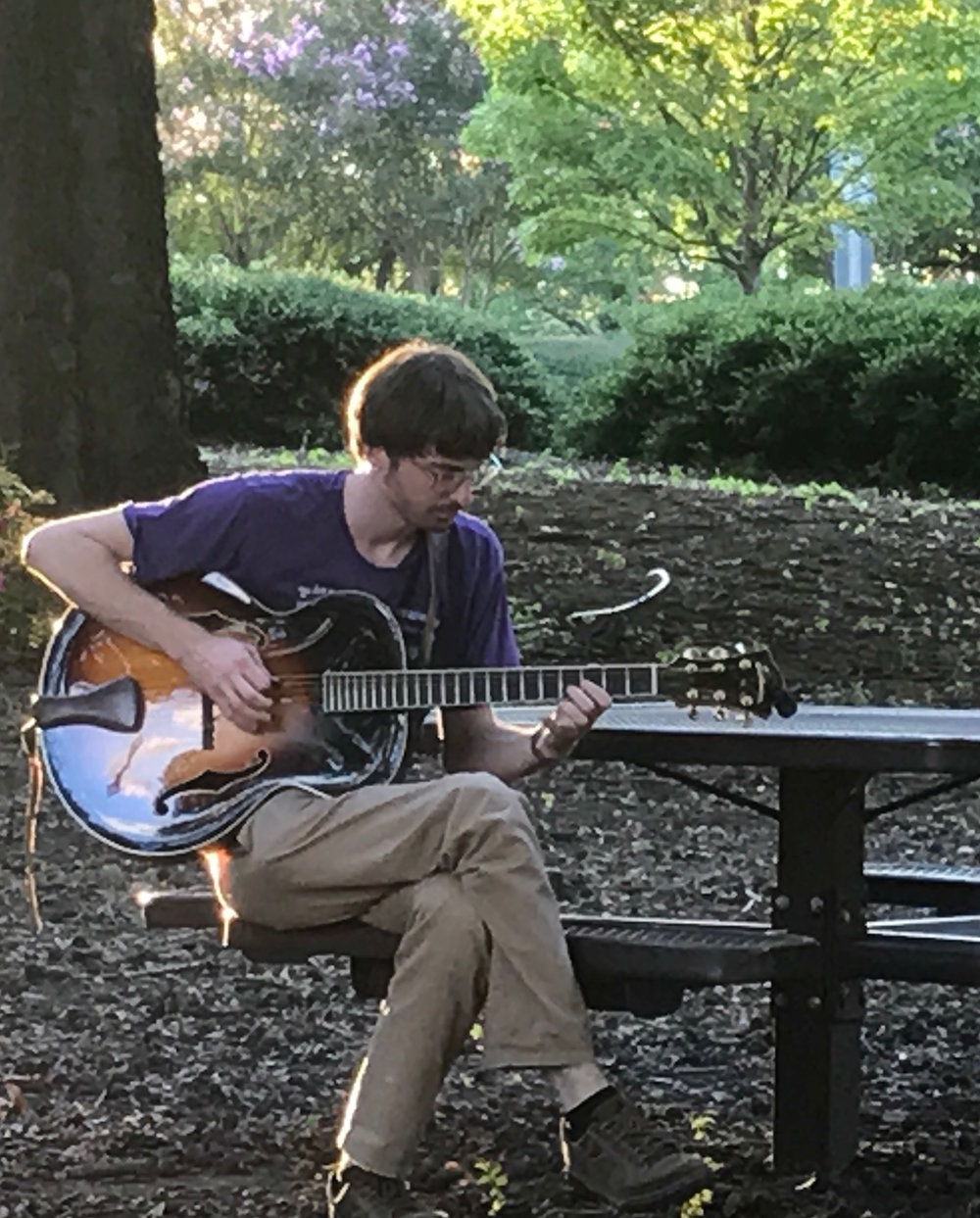 Eli strumming at a park in Birmingham, AL