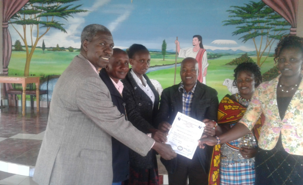 John (center) receives award from Community Leadership in Ewaso Ngiro
