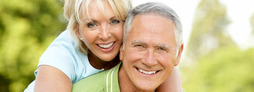 Elderly couple hugging and smiling - dental implants