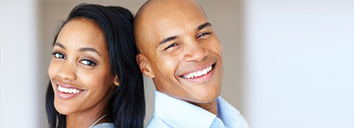 Smiling couple back to back - family dentistry