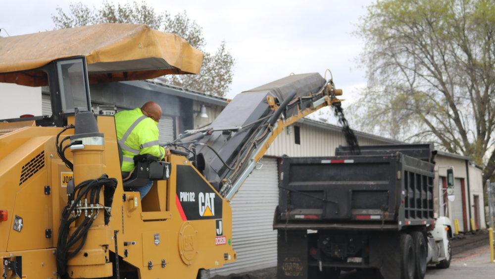 Grinder Milling Asphalt Into A Dump Truck