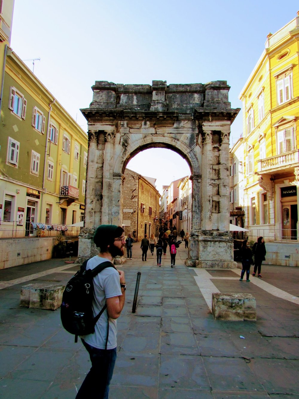 Emmett about to walk through the Arch of Sergii, a Roman triumphal arch in downtown Pula.