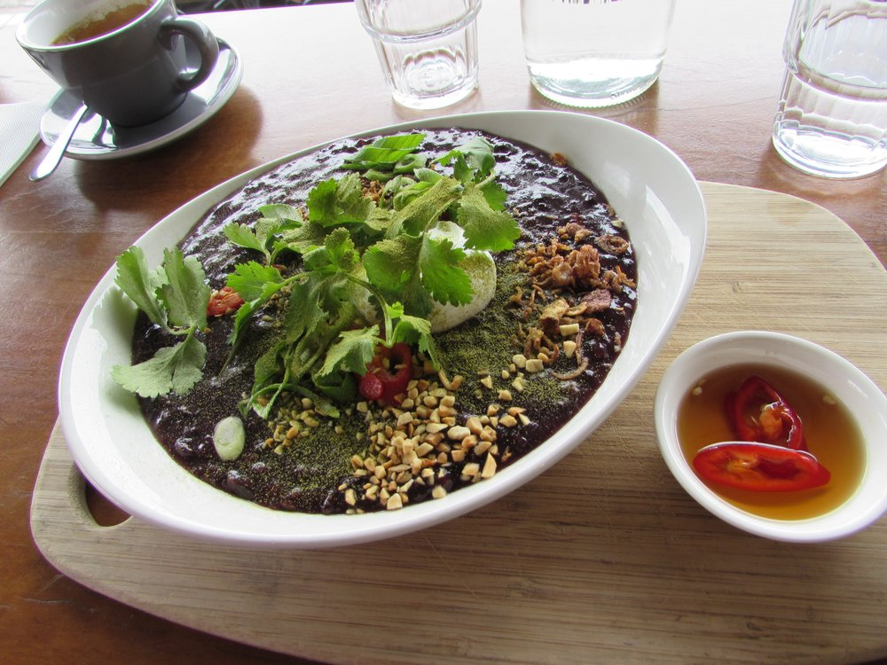 Breakfast from  Short Round  in Thornbury. Black rice congee with lemongrass, peanut bits, poached egg, and chili oil on the side. Excellent.