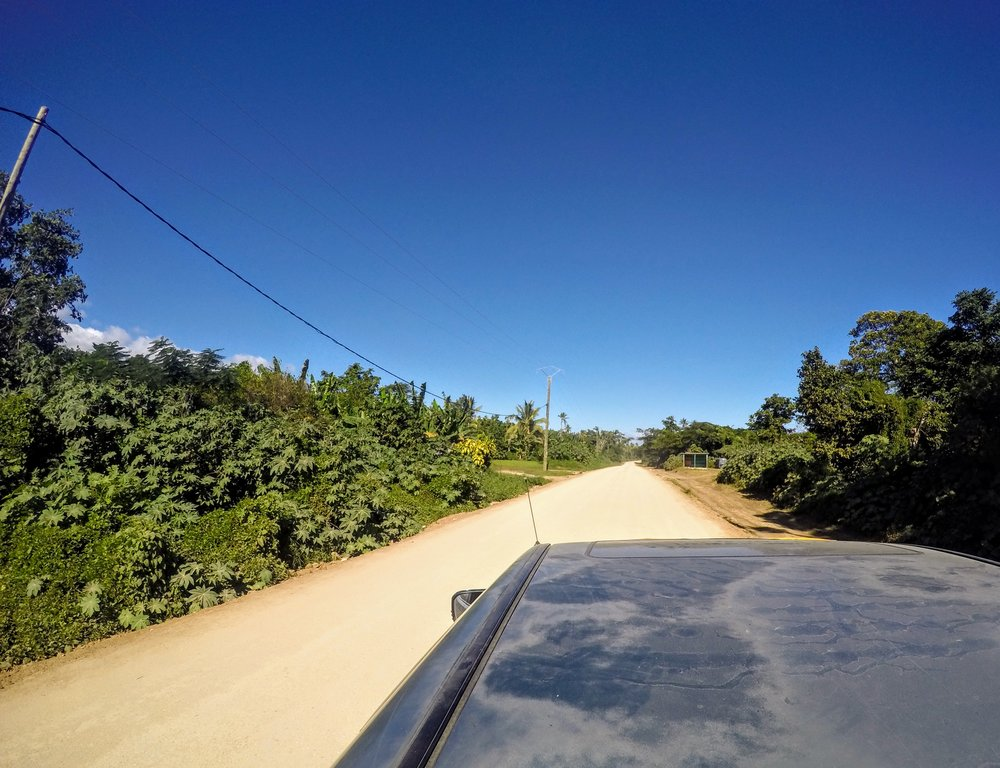 Tanna's unsealed road, looking out over the truck's cab from our bench seat.