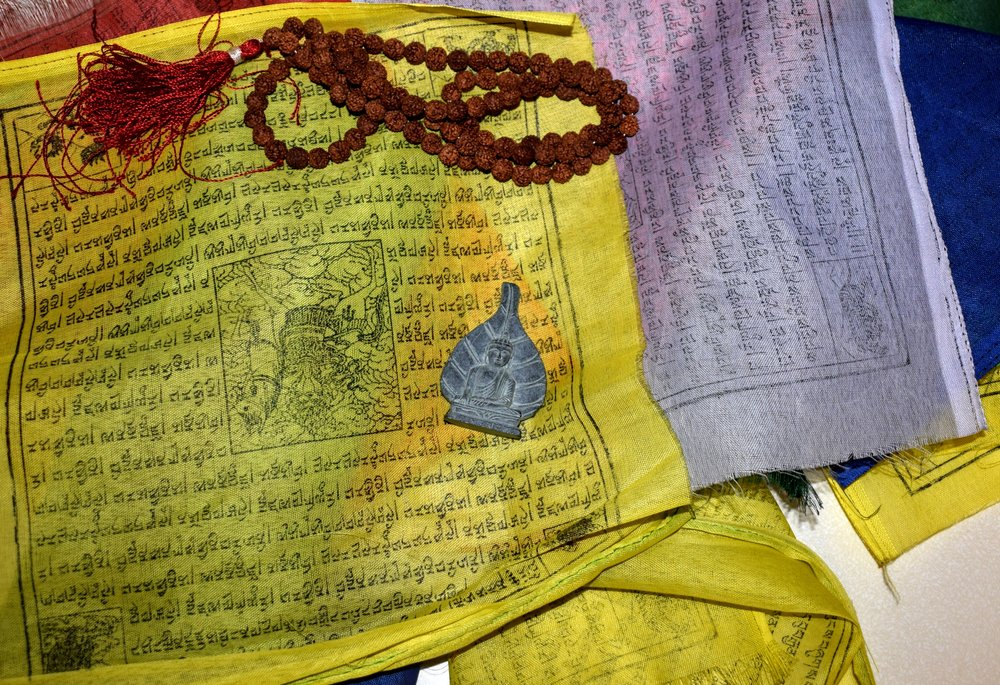 Some souvenirs we picked up in Nepal: a small hand-carved stone boddhisatva from Lumbini, large prayer flags & beads from Swayambhunath.