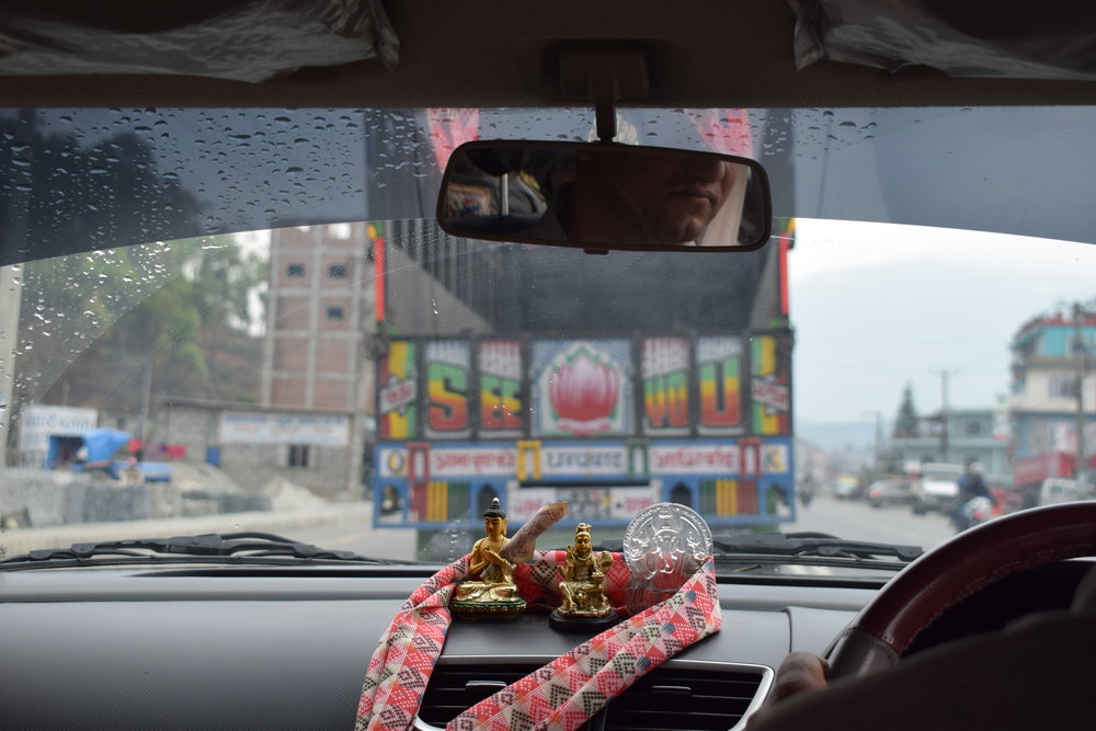 """The back of a colorful truck that says """"SEE YOU"""" as seen from a taxi near Pokhara, Nepal."""
