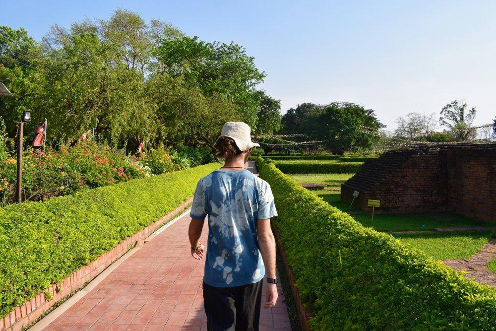 Emmett walks along the brick path outside the Maya Devi Temple complex.