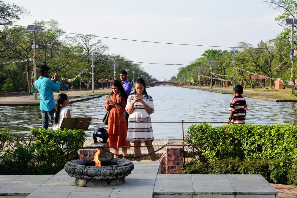 Young tourists take a photo of the Eternal Peace Flame in Lumbini