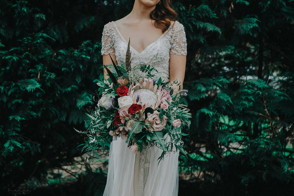 Wild protea bouquet with feathers, dusky pink and red roses, lavender, jasmine and hellebore. Captured by  Bianca - Love Stories