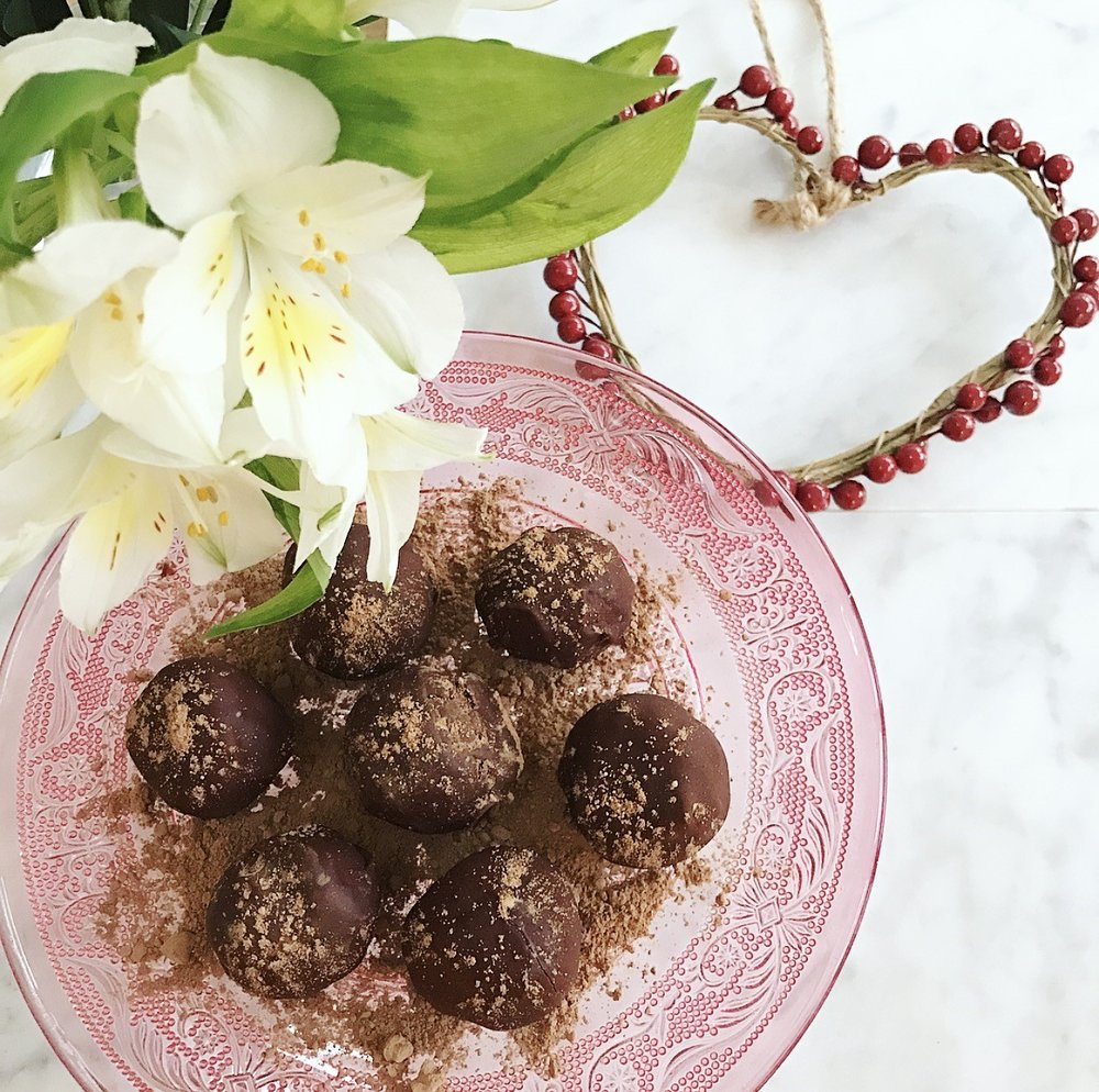 Ingredients:  For the truffles: 12 medjool dates (pitted) 3 tsp cacao powder zest of one orange 50 g almond butter (the solid bits work best in this recipe) 1 tbsp freshly squeezed orange juice  For the chocolate: 50g cacao butter 15g cacao powder 2 tbsp maple syrup or coconut nectar pinch of salt 3 drops of orange essence  Method:  1. Place the dates into to food processor and blend first. 2. Add the cacao powder, orange zest, almond butter and orange juice and blitz until a dough-like texture forms.  3. Roll the mix into balls and place in the freezer for about 20 minutes. 4. In the mean time, melt the cacao butter over a very low heat, once melted add the cacao powder, maple syrup or coconut nectar, salt and orange essence and stir until smooth.  5. Remove the truffles from the freezer and coat each one in the chocolate, return them to the freezer for another half an hour and re-coat. Return the truffles to the freezer for about 2 hours to fully set. Serve and enjoy!