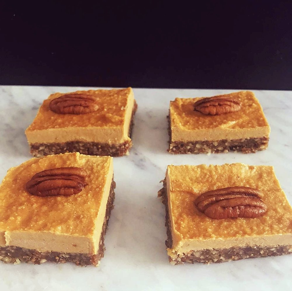 Ingredients: (makes about 6 squares)  Base: 100g raw pecans 80g dried and partially rehydrated figs (you can always just soak dried figs in water for 4 hours if you can't buy them).  1 tsp vanilla extract (no added sugar) Coconut oil for greasing dish  Cheesecake layer: 100g raw cashews (soaked in water for 6 hours) Juice of 1 orange 1 tsp vanilla extract (no added sugar) 3 tsp goji berry powder Maple syrup to taste (optional)  Pecans for decorating.  Method: 1. Blitz the pecans in a food processor to break them down.  2. Chop the  hard stalk off the figs and add them to the food processor with the pecans and the vanilla. Blitz until a dough texture is formed.  3. Grease a brownie tin with a small amount of coconut oil to prevent sticking. Press the mix into the base of the tin ensuring that the base is even. You want it to be about 1/2 cm thick. Place the tin into the freezer whilst you make the filling. 4. Blitz the cashews in the food processor, once broken down add the orange juiceand vanilla extract and continue to blend until smooth. Then add the goji berry powder and the maple syrup if using.  5. Once fully combined, add the filling to the base and smooth it out. Strategically place the pecans on top of the filling and return to the freezer for 4 hours before slicing and serving.  6. Enjoy!