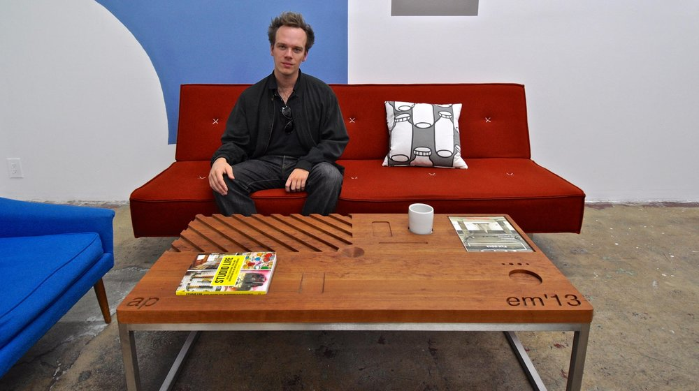 Artist Emmett Moore sits behind his 2013 work Numerical Control Table at Gallery Diet.