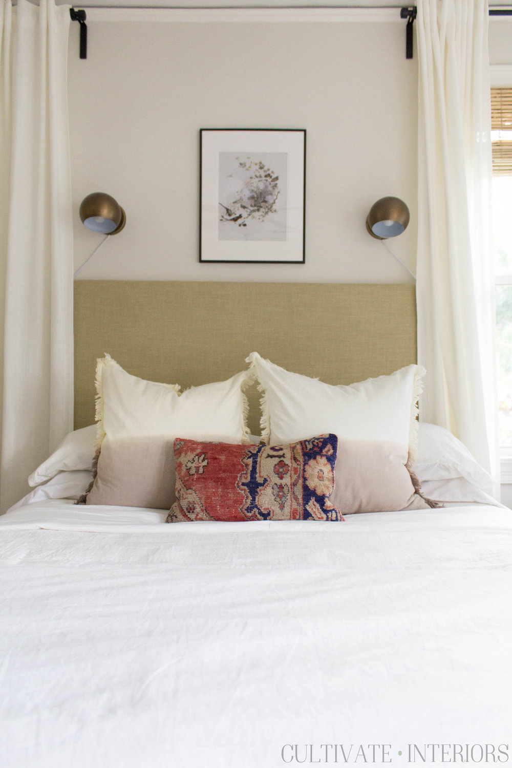 Red kilim pillow layered with fringed euro pillows and white bedding, eyeball sconces, and green headboard