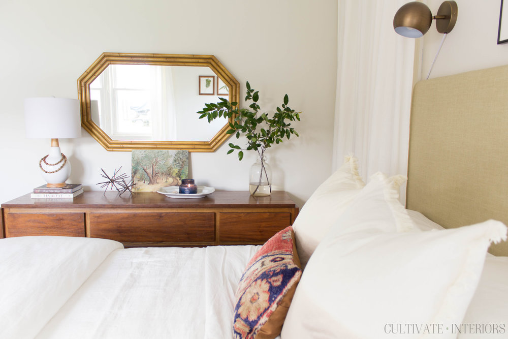 Vintage accessories, dresser, and eclectic natural bedding