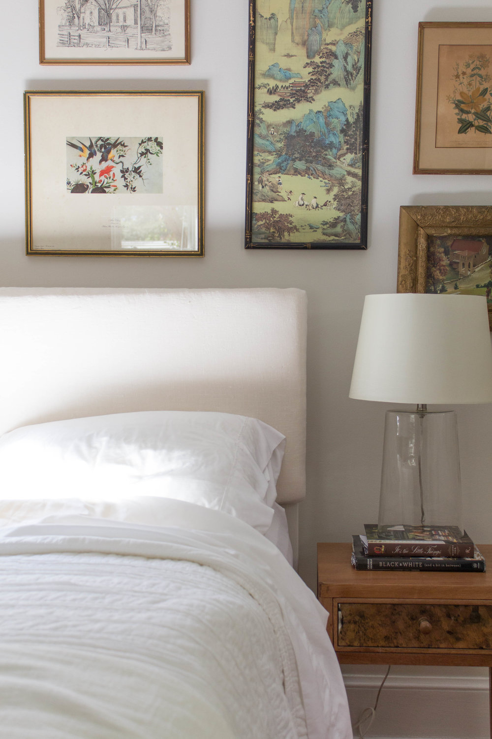 Gallery wall of vintage art with glass lamp and white bedding