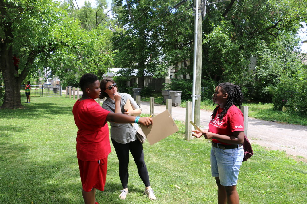 Students Kevon Bonds and Makayla Wallace discuss their chosen site with Adriana Keramida-Strahl during the class' first visit to the pocket park.